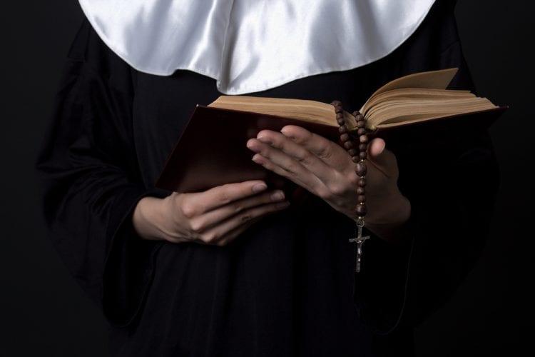 A nun holding a prayerbook | Investment U
