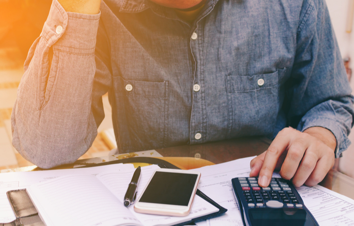 how-to-pay-off-debt-fast-man-using-calculator