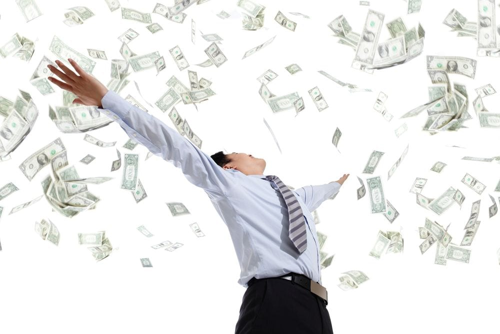 It's raining cash down on a man in business dress | Investment U