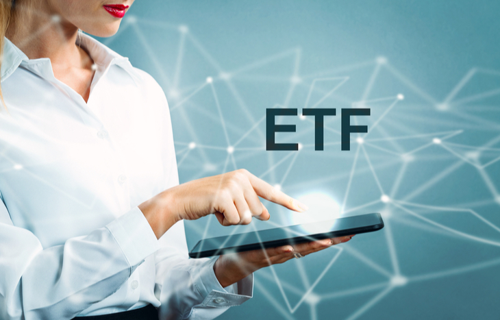 Touching a tablet searching how to invest in an ETF