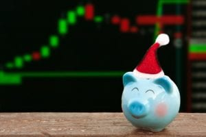 "A piggy bank with a Santa cap in front of a stock chart - ""NASDAQ Holidays 2019-2020"" 
