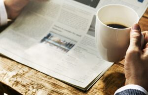 A person drinks coffee while reading an investment newsletter at a table