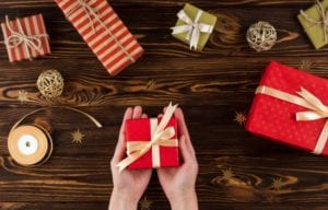 Christmas presents on a table with hands holding one