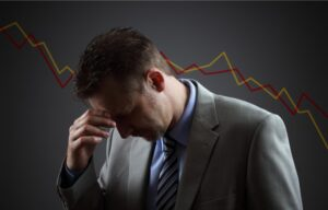 A sad investor looks down with his hands on his forehead. Is the stock market going to crash?