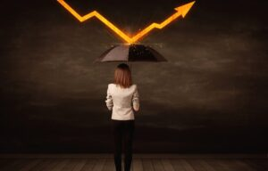 A woman holds up an umbrella to minimize her risk. How does diversification protect investors from risk?