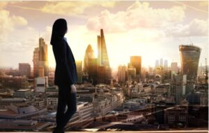A business woman looking out over a city skyline at investment opportunities during a stock market correction at sunset | Investment U