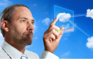 A business man touches a cloud on a computer display. He may be interested in these cloud computing stocks to buy now.