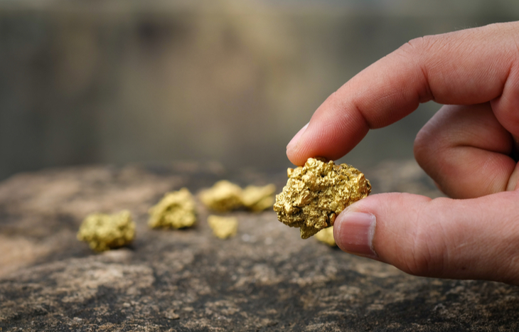 holding a gold nugget as prices and gold mining stocks increase
