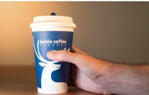 A hand holding a cup of Luckin' coffee. But will investors of Luckin Coffee stock be left holding the bag?