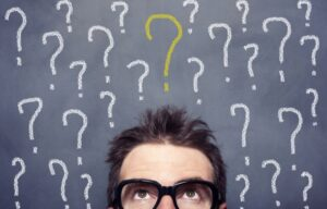 Why is the stock market a man wonders amid a blackboard of question marks.