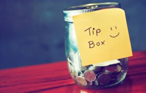 "A tip jar with a post-it note that says ""tips here"" for investing tips."
