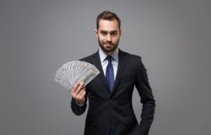 A twenty-something man in a business suit holding a fan of cash is building wealth in his twenties.