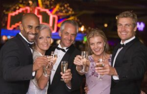 Five wealthy people dressed up nicely and drinking - wealth creation