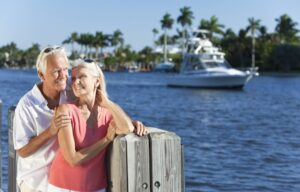A happy wealthy couple cuddling on the docks - wealth creation tips
