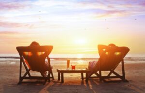 A wealthy retired couple that has been building wealth in their 70s is now relaxing in recliners on a beach at sunset.