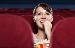 A woman sits alone watching a movie in a theater. Will AMC stock continue to perform?