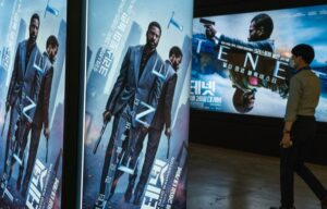 A movie goer walks by posters from Tenet, which has seemingly failed to save AMC stock in the short term.