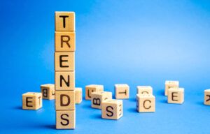 "A stack of blocks against a blue background. The blocks spell out ""trends"" symbolizing trending stocks."