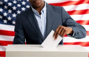A man dropping a ballot into a voting box. But will this Presidential Election affect the stock market?
