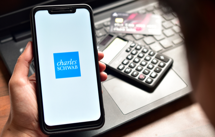 looking at a Charles Schwab review on a smartphone