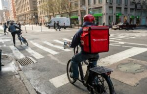 A doordash dasher rides his bike to deliver something as the stock IPOs on the new york stock exchange.