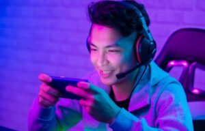 A young man playing mobile games on his iphone like Skillz Inc. gaming platform IPOs his shares