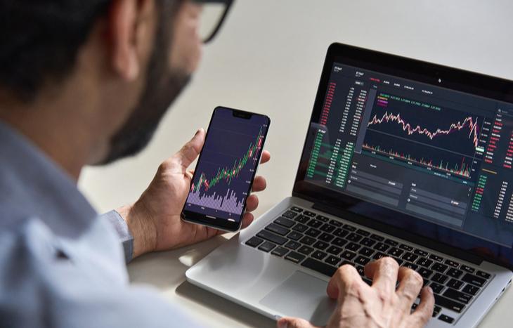 Hombre intercambiando criptomonedas GeroWallet en su computadora y teléfono.